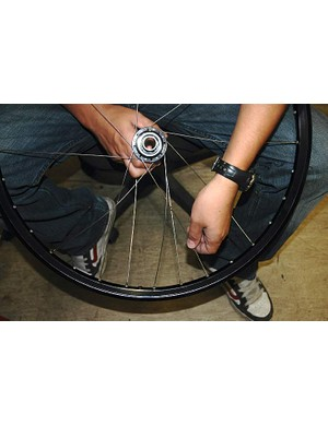 Complete this side of the wheel by inserting a spoke up through the flange two holes counter clockwise from the one already upwards in the hub.