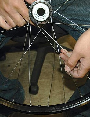 With the hub disc side down, put a spoke in downwards, two holes counter clockwise from the one already downwards in the hub.