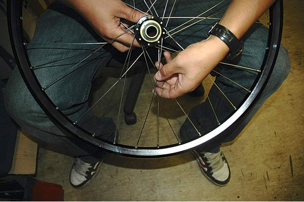 Put the spoke into the rim four eyelets clockwise from the valve hole, lacing over two spokes and under a third.