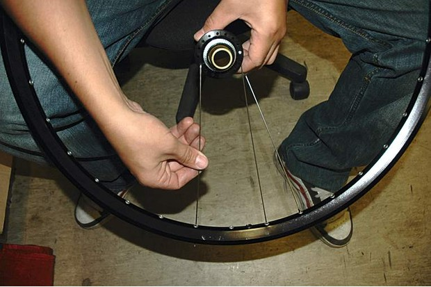 Count seven holes clockwise from the spoke in the disc side flange, then insert a spoke up through that seventh hole.