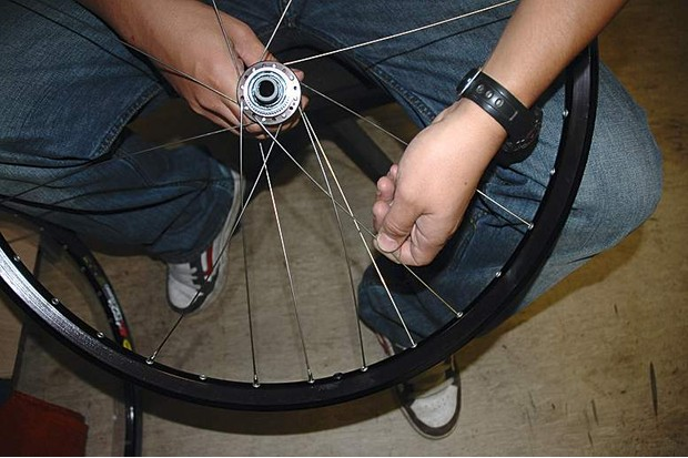 Complete this side of the wheel by inserting a spoke up through the flange two holes counter clockwise from the one already upwards.