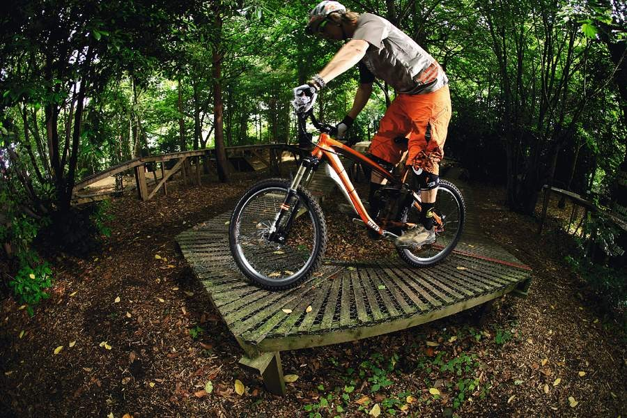 Turn the front wheel at the very last minute in order for the rear wheel to clear the turn without dropping off the ladder