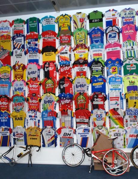 Museeuw bikes await assembly in front of a vast wall of jerseys in the Centrum Ronde Van Vlaanderen.