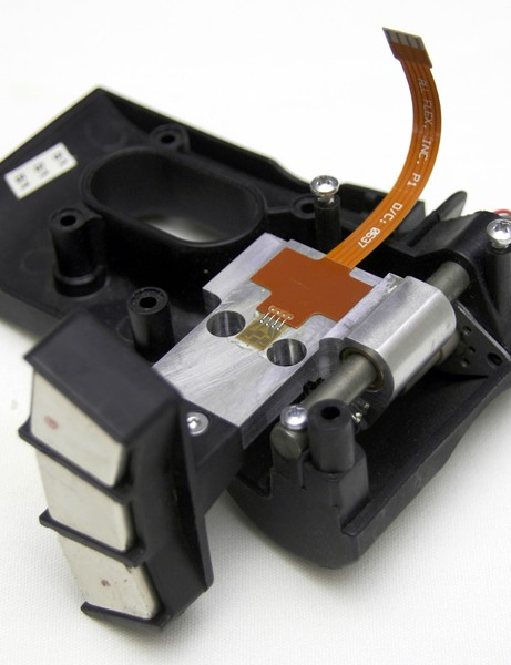 The linear stepper motor simply alters the distance from the magnets to the conductive zinc flywheel, thus altering the strength of the magnetic field and resistance.