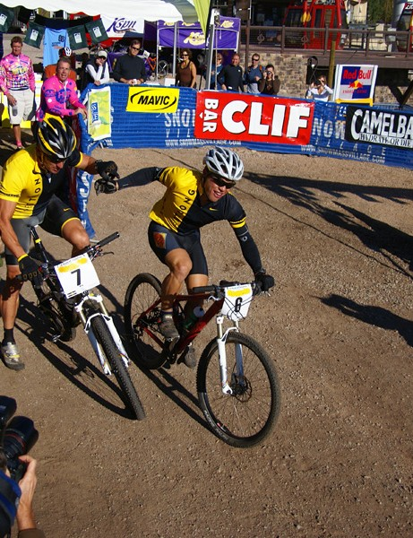 Taam comes into the transition area to tag Armstrong and puts the Livestrong team in first place.