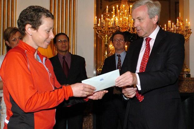 Jane Tomlinson (L) receives a donation from British ambassador to France Sir John Holmes