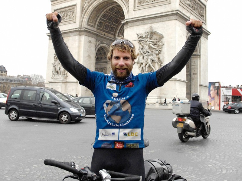Marc Beaumont celebrates his achievement in front of the  Arc of Triomphe in Paris