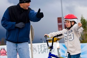 A young cyclist receiving bike safety instruction with his new bike.