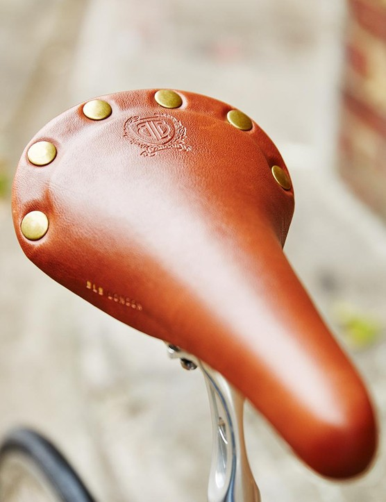 The vegan leather saddle has a classic brass rivet look