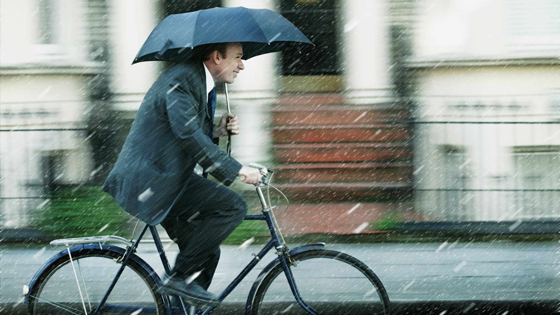 While there are many features that indicates this might be a British cyclist, realistically they are unlikely to be smiling in these conditions. Even though it gives them something to talk about to other cyclists/people at work.