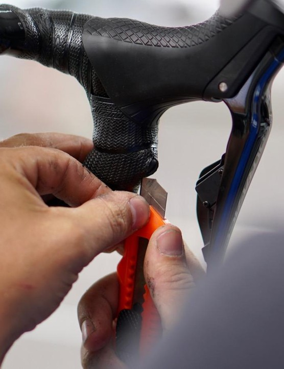 After wrapping the tape snugly around the sprinter shifters, Cavendish's mechanic makes a small incision over the button