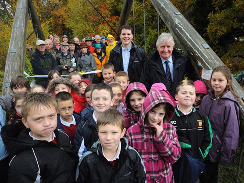 Celebrations mark completion of Clydach Gorge walking and cycling route. Heritage Minister Alun Ffred Jones AM (R) beside plaque to commemorate the opening of the stunning new Clydach Gorge walking and cycling route to mark its transformation from a disused railway line. (Thursday 13 November) . Also, braving the weather is Lee Waters, Director of Sustrans Wales (centre), local people & children from Govilon Primary School.