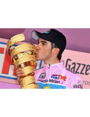 Contador and his Giro prize, a minitaure golden bronze parking ramp.