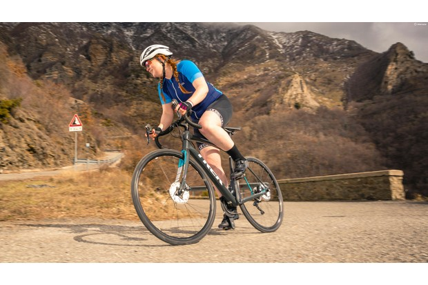 Woman in a blue jersey riding a road bike on a mountain road