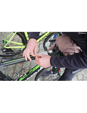 A Dimension Data mechanic applies the course notes ahead of race sign on