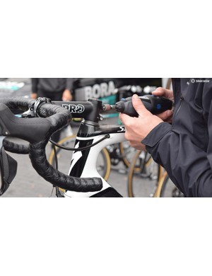 A Bora-Hansgrohe mechanic files down stem bolts the day before the race
