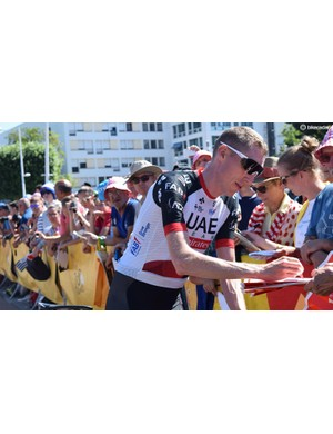 UAE Team Emirates' Dan Martin signs autographs for fans ahead of stage five