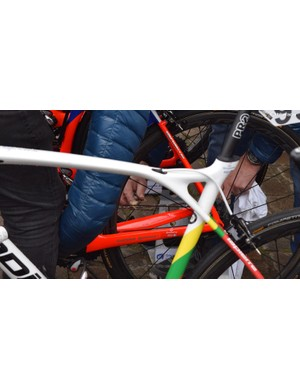 A Groupama-FDJ mechanic applies a waxy chain lube by hand to a rider's bike at the race start