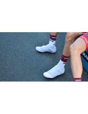 Some riders choose not to wear sponsor correct shoes and cover up their preferred shoes with oversocks