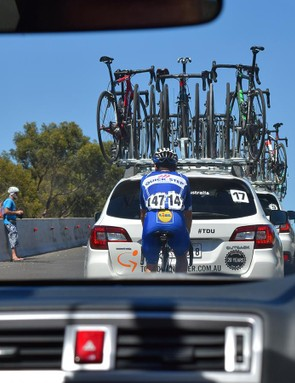Enric Mas of Quick-Step Floors works his way through the team cars to rejoin the bunch