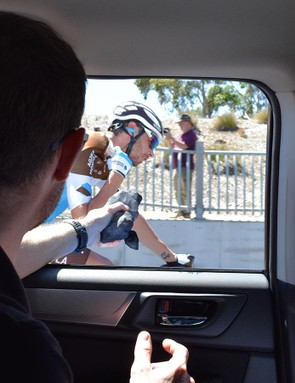 Mechanic Michael Szkolnik passes ice filled stockings to the riders to help battle the heat