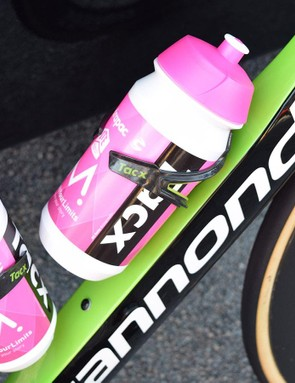 Pink team bidons are paired with green Tacx Ciro bottle cages