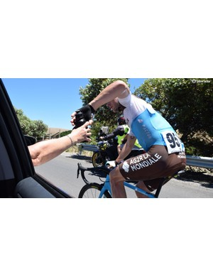 Nans Peters drops back for more bidons from Laurent Biondi