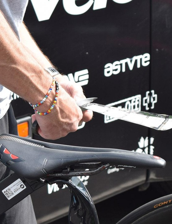 A Dimension Data mechanic cuts pre-prepared course notes ready to be stuck to riders' stems for the stage