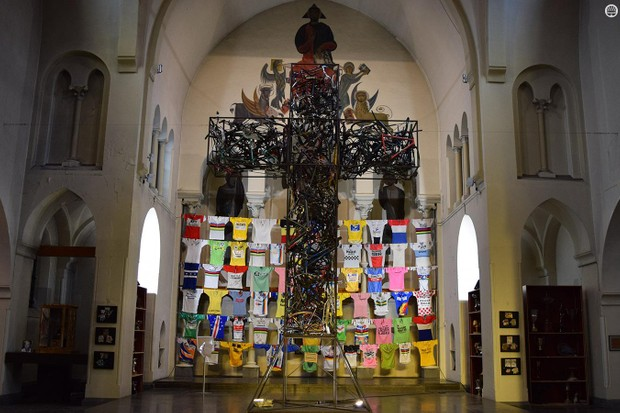An 'iron cross' consisting of hundreds of welded bicycles and parts sits at the head of the church with the wall of jerseys as a backdrop