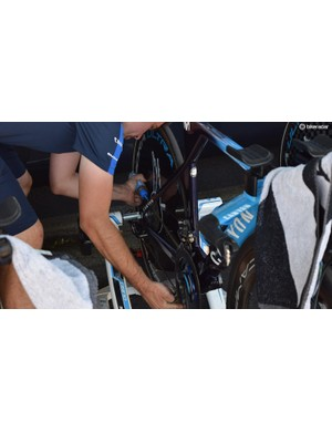 A Movistar mechanic adds some final chain lube to a team bike ahead of the stage