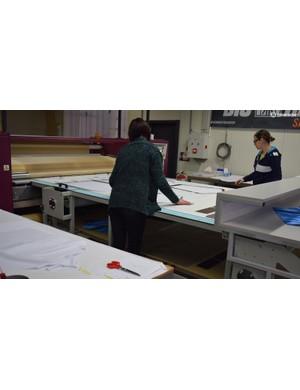 Massive printers sublimate the jersey designs onto the white base fabrics