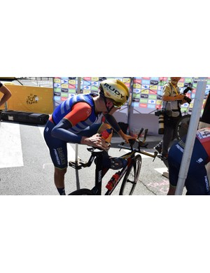 Heinrich Haussler stretches out ahead of the stage while wearing an ice vest ahead of the stage