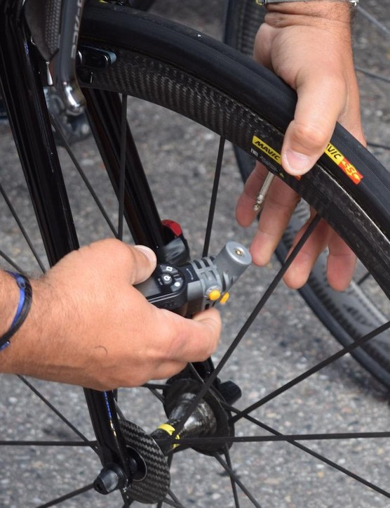 A mechanic checks Talansky's tyre pressures with a digital gauge ahead of the stage