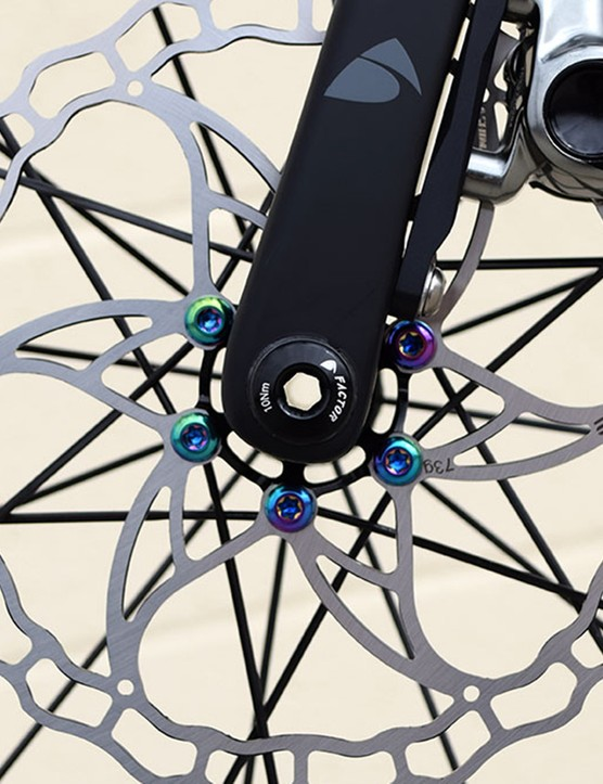 The lightweight Ashima rotor is paired with some decadent rainbow Ti bolts