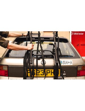 Start by opening up the bike rack and placing it carefully on the boot of the car, in the middle