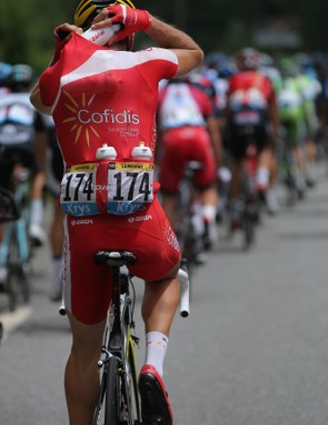Cyril Lemoine of Cofidis collects water bottles from the team car for his fellow riders