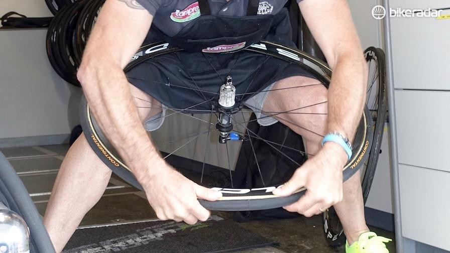 Bacchion places the last section of tyre on the rim, straightening it in the process
