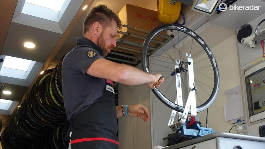 This is Lampre-Merida's Moreno Bacchion. On a rainy morning before the start of Stage 2 he was busy working, keeping his inventory of race wheels tip top. Graciously he let us photograph him while he worked. Here he scrapes excess dried glue off the rim using a utility knife. He also quickly checked that the wheel was true