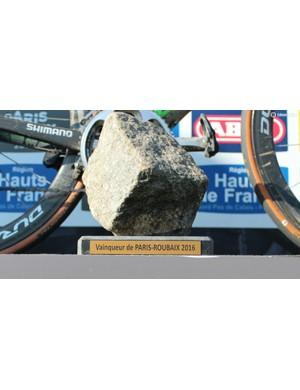 Win a very hard bike race, get a very big rock