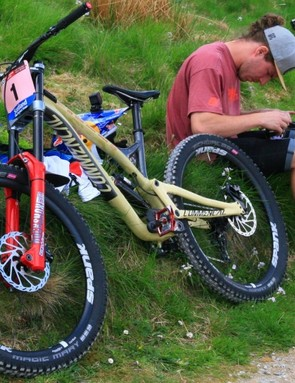 Myriam Nicole's Commencal Supreme DH V4.2 sits beside her mechanic, prepping her goggles. Nicole chose the 27.5in bike for Fort William, rather than the new 29er that Commencal also offers