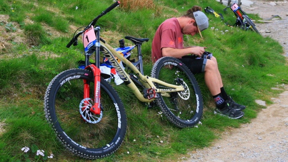 7ef9ee6e02f Myriam Nicole's Commencal Supreme DH V4.2 sits beside her mechanic,  prepping her goggles
