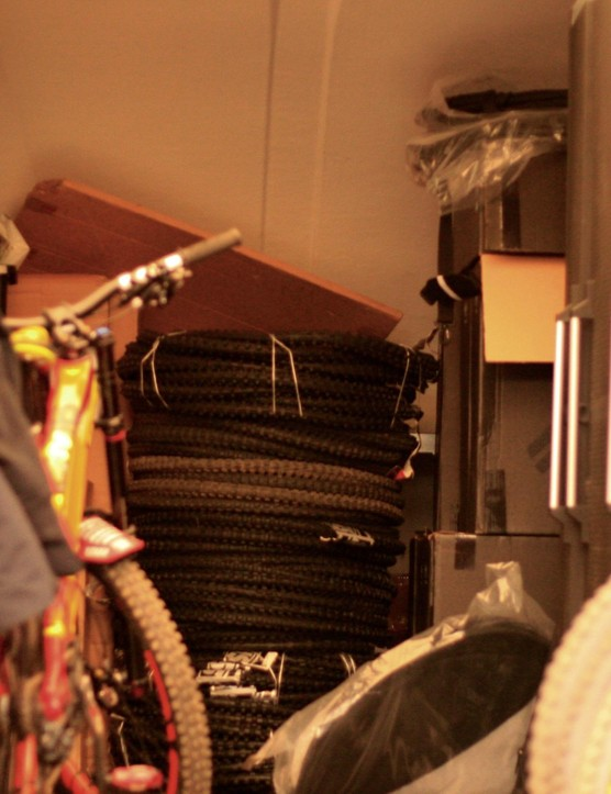 The back of the truck has well-ordered spares and a huge pile of tyres waiting to go