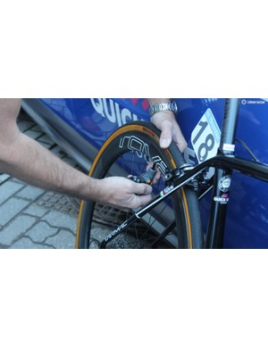 A Quick-Step mechanic checks Matteo Trentin's tyre pressures with a digital gauge