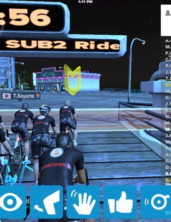 Having joined a group ride, riders wait at the start for it to begin. The ride-specific chat scrolls at right and a mobile-specific menu is shown at bottom
