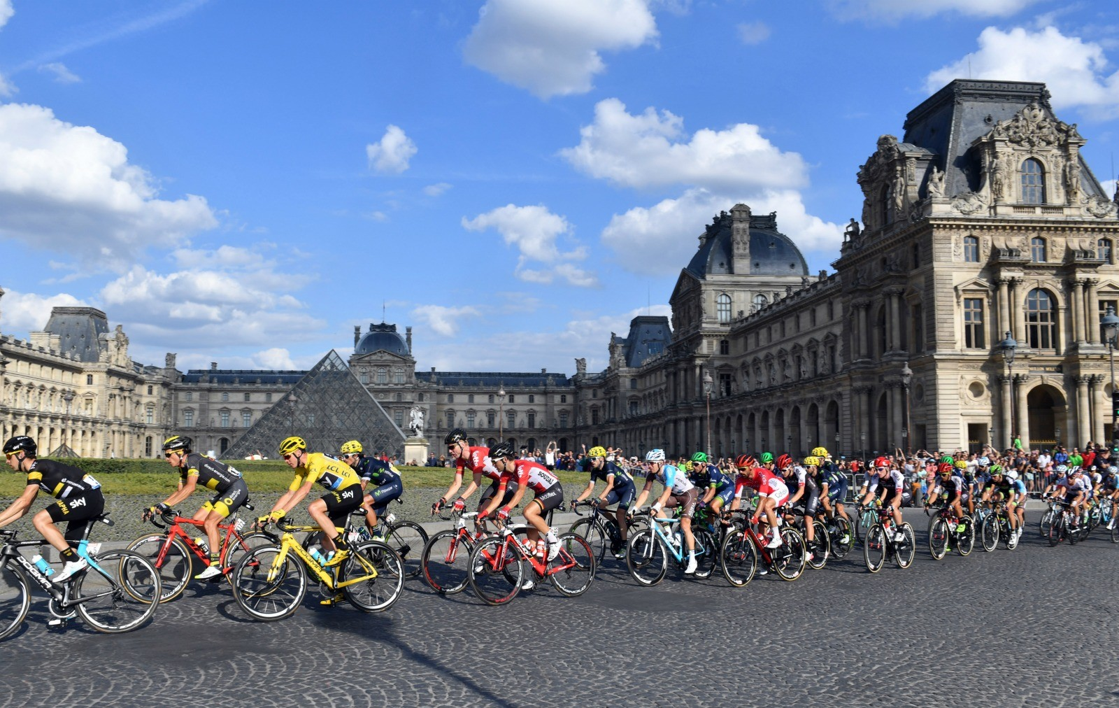 Chris Froome rides past the Louvre in the yellow jersey