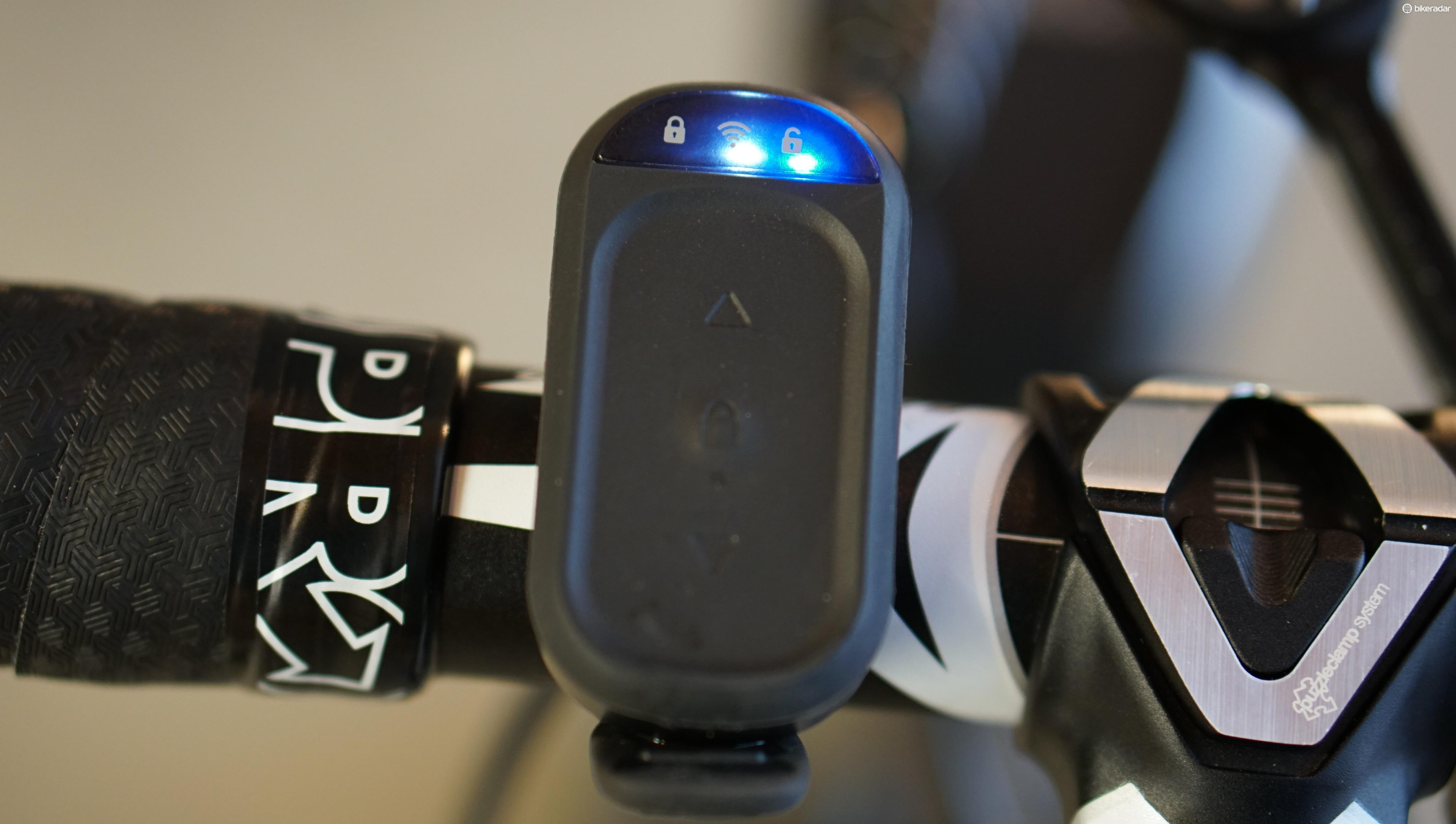The remote toggles between unlocked (shown with blue light at right) to work with Zwift, TrainerRoad or other third-party apps, and locked (which is the unlit icon at left). The white light shows that the Climb is connected to a Kickr