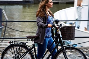 The bike is fitted with a pannier rack and deep front basket with a supporting frame