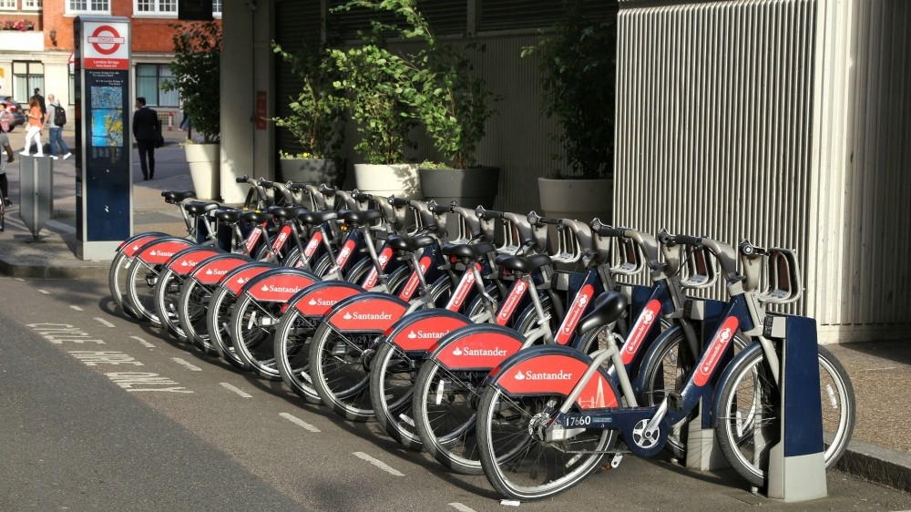 An example of a docking station, with bikes parked at each dock and a kiosk from where you can purchase a hire period and get the release code