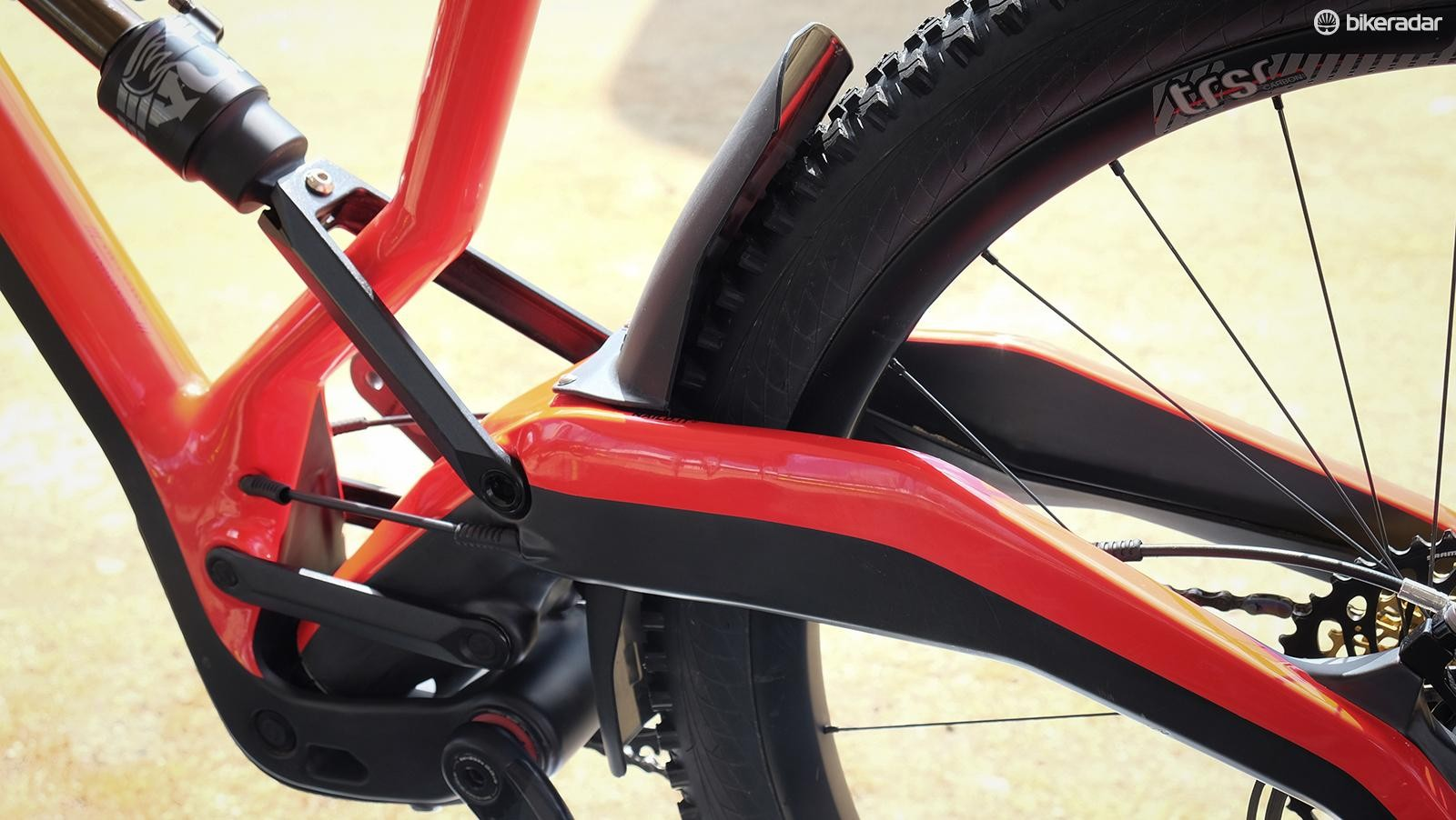 An integrated rear fender is required to trail debris off the linkage