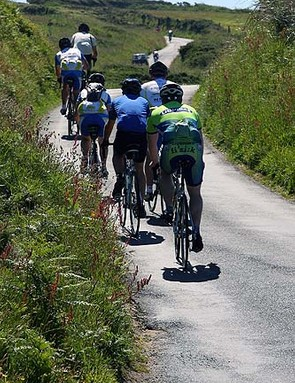 Riders make their way up the sun-drenched lanes